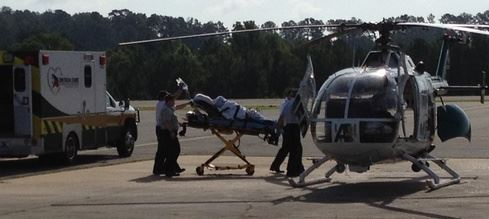 Emergency staff load a stretcher onto a helicopter.