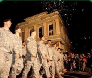 Soldiers marching down the street with fireworks in the sky.