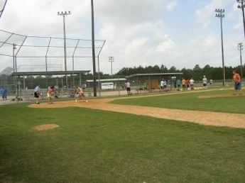 Men and women playing softball together on a softball diamond.